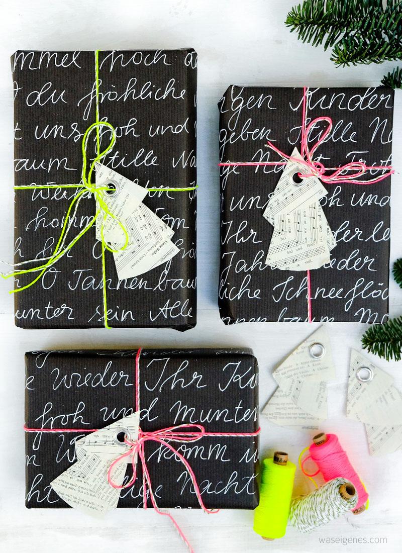 DIY Weihnachtsbaum Geschenkanhänger | aus den Seiten eines alten Gotteslobes falten, Notenpapier, eine Öse einschlagen | schwarzes Geschenkpapier Handlettering, neon Garn | waseigenes.com DIY Blog