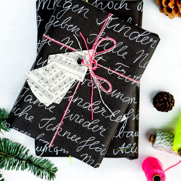 DIY Weihnachtsbaum Geschenkanhänger | aus den Seiten eines alten Gotteslobes falten, eine Öse einschlagen | schwarzes Geschenkpapier Handlettering, neon Garn | waseigenes.com DIY Blog