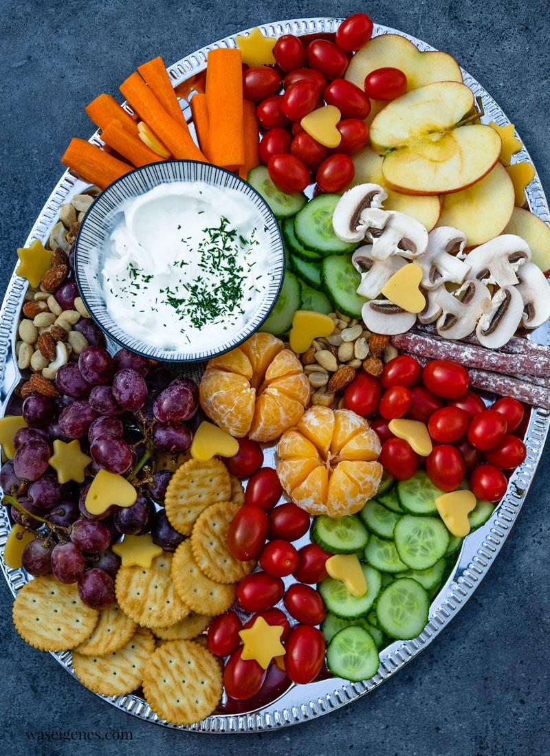 Bunte Platte: Äpfel, Tomaten, Gurken, Mandarinchen, Cracker und Nüsse, waseigenes.com